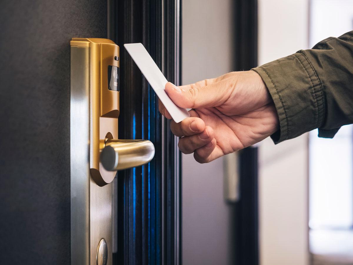 hand holding keycard to door lock